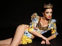 Женщина с темными волосами в роскошном платье золота с bijou и кроной, Стоковые Изображения