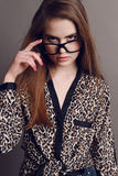 Женщина с темными волосами в элегантной рубашке печати леопарда и с стеклами Стоковые Изображения RF