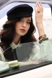 Женщина с темными волосами в элегантных одеждах сидя в автомобиле Стоковая Фотография