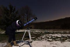 Женщина с телескопом под женщиной ночного неба зимы смотря через телескоп под звездной ночью стоковые фото