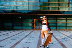 женщина с телефоном и longboard внешнее Стоковые Изображения