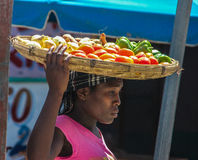 Женщина с товарами в корзине на голове Стоковое фото RF