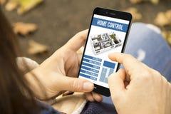 Женщина с умным домашним управлением app на парке Стоковые Изображения RF