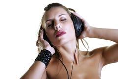 Женщина слушая к музыке используя наушники Стоковое Фото