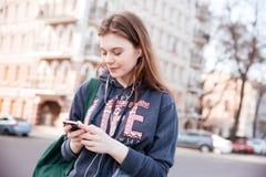 Женщина слушая к музыке и используя сотовый телефон на улице Стоковое Фото