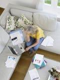 Женщина с финансовыми документами и компьтер-книжкой Стоковая Фотография