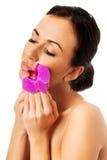 Женщина с фиолетовой орхидеей и закрытыми глазами Стоковое Изображение