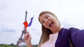 Женщина с французом сигнализирует около Эйфелева башни делая selfie Усмехаясь туристская женщина путешествуя в Европе сток-видео