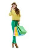Женщина с хозяйственными сумками говоря smartphone на белой предпосылке Стоковая Фотография RF