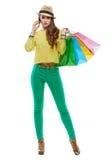 Женщина с хозяйственными сумками говоря smartphone на белой предпосылке Стоковые Изображения RF