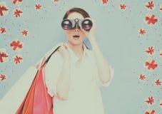 Женщина с хозяйственными сумками и бинокулярное Стоковые Фотографии RF