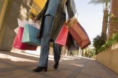 Женщина с хозяйственными сумками идя на мостоваую Стоковое Изображение RF