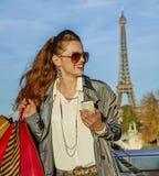 Женщина с хозяйственными сумками и smartphone в Париже смотря в сторону Стоковое фото RF