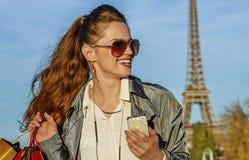 Женщина с хозяйственными сумками и smartphone в Париже смотря в сторону Стоковое Изображение RF