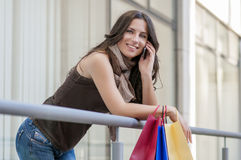 Женщина с хозяйственными сумками на телефоне Стоковое фото RF