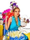 Женщина с цветками в стиле пасхи волос держа яичка и цветки Стоковое Фото