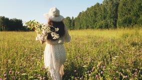 Женщина с цветками идет в луг видеоматериал