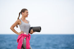 Женщина с циновкой для фитнеса на побережье Стоковая Фотография