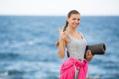 Женщина с циновкой для фитнеса на побережье Стоковые Фото