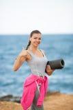 Женщина с циновкой для фитнеса на побережье Стоковые Изображения RF