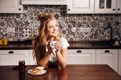 Женщина с чашкой в кухне стоковые изображения rf