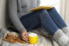 Женщина с чашкой горячего какао читает книгу на подоконнике Стоковое Фото -  изображение насчитывающей какао, чашкой: 158718518