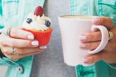 Женщина с чашкой капучино и частью десерта на плите, мягкой предпосылки фокуса Стоковое Изображение