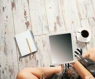 Женщина с чашкой кофе, блокнотом и таблеткой Стоковые Фотографии RF