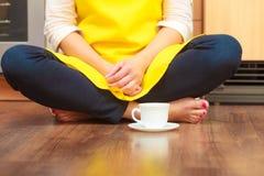 Женщина с чашкой кофе в кухне Стоковые Изображения