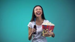 Женщина с чашкой попкорна задушевно смеясь наблюдая комедией и питьевой содой акции видеоматериалы