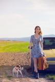 Женщина с чемоданом и собакой около автомобиля Стоковые Изображения