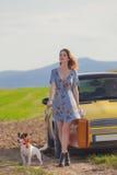 Женщина с чемоданом и собакой около автомобиля Стоковые Изображения RF