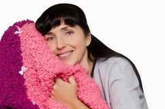 Женщина с черными длинными волосами с улыбкой, который нужно snuggle для того чтобы греть шотландку изолированную на белой предпо стоковое изображение