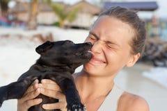 Женщина с черным щенком в руках Стоковые Изображения
