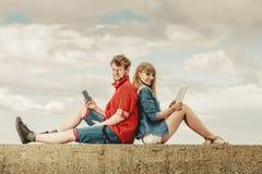 Женщина с человеком smartphone с парами таблетки внешними Стоковое Изображение RF