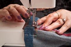 Женщина с швейной машиной и кромкой голубых джинсов Стоковое Изображение