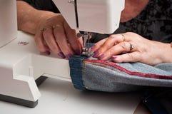 Женщина с швейной машиной и кромкой голубых джинсов Стоковая Фотография RF