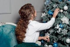 Женщина с шикарными волнистыми волосами украшая дерево стоковые изображения