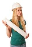 Женщина с шлемом конструктора и план строительства счастливый для того чтобы сделать Стоковое Фото