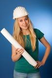 Женщина с шлемом конструктора и план строительства счастливый для того чтобы сделать Стоковое Изображение RF