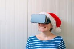 Женщина с шляпой Санта Клауса рождества и шлемофоном VR Стоковые Фотографии RF