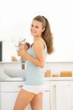Женщина с электрической зубной щеткой в ванной комнате Стоковые Фотографии RF