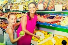 Женщина с яблоками девушки покупая Стоковые Изображения