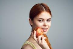 Женщина с яблоком, диетой, здоровой едой, женщиной держа яблоко на серой предпосылке Стоковые Фотографии RF