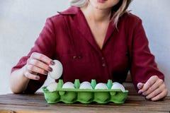 Женщина с яйцами цыпленка в коробке на деревянном столе стоковое фото