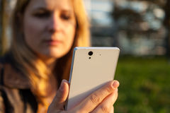 Женщина с apathetically смотрит на и smartphone Стоковые Изображения