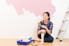 Женщина с paintbrush в руке и картине Стоковое Фото