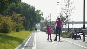 Женщина с rollerblades езды дочери в парке сток-видео