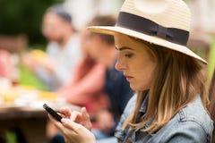 Женщина с smartphone и друзья на лете party Стоковая Фотография