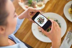 Женщина с smartphone фотографируя еду на кафе стоковое фото rf